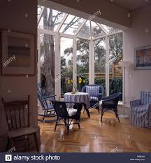 parquet flooring and wicker chairs in an open plan glass