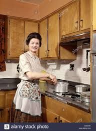 1960s smiling woman housewife wearing an apron stirring cooking