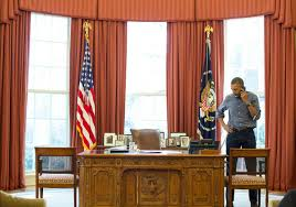 president barack obama talks on the phone in the oval office with