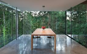 glass box dining room cantilevers out towards cedar forest home