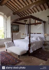 white chaise longue below simple four poster bed with crisp white