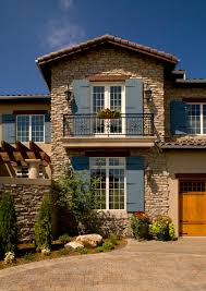 faux wood shutters exterior mediterranean with balcony boulders