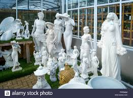 a collection of garden ornament statues for sale in a garden
