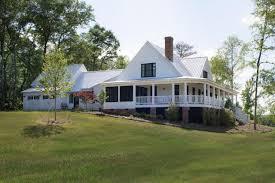 spacious white modern farmhouse with wraparound porch from cozy