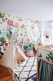 sweet floral wallpaper and moroccan rug mix in this kids room