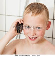 pretty verry young boys washing hairs young boy shower while holding cellphone stock photo 568417897
