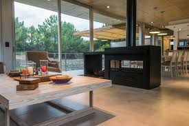 concrete ceiling interiors living room with black metal double sided fireplace as