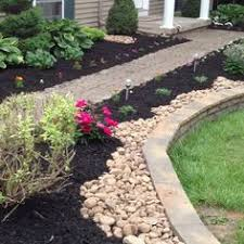 landscaping around patio with river jack rock covering down spout