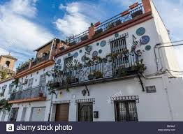 row of white spanish houses in granada with balconies full of