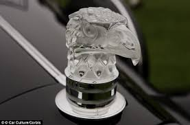 collection of glass mascots displayed on car bonnets in