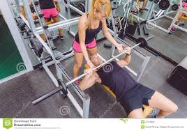woman coach helping to man in bench press training stock photo