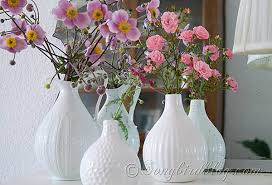 White Vases Decorating With Garden Flowers In Pink And Yellow And Three White