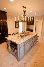 rustic chandelier over white marble top kitchen island with