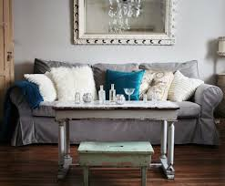 gray sofa with soft blue gray walls and vibrant turquoise pillow