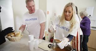 friendly voluntary workers standing at a soup kitchen serving