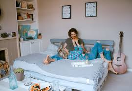 young couple room young couple on bed feeding each other pizza with fireplace