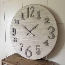 large round coastal whitewashed cream wood clock by cowshed