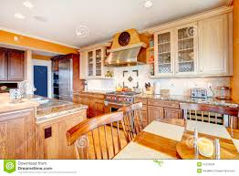 brown and yellow kitchen with dining table set stock images