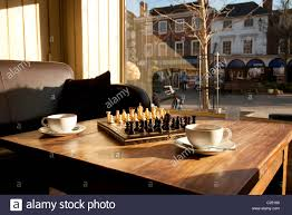 chess board coffee table game of chess set out on a coffee table with two cups stock photo