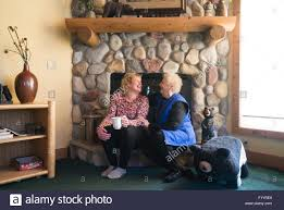 two happy blond caucasian women sit on a fireplace ledge laughing