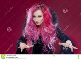 pink halloween background free scary witch with red hair performs magic on a pink background