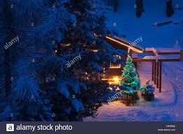 christmas tree outdoor decoration in a snowy night with gifts and