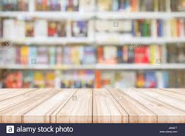 empty wooden table top with blur bookshelves in bookstore