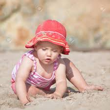 cute caucasian baby playing with sand on stock