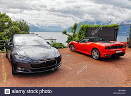 convertible ferrari a tesla s electric sedan and a red ferrari convertible car parked