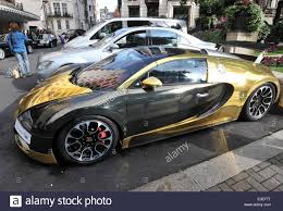 car bugatti gold passers by stop to check out two flashy cars parked outside the