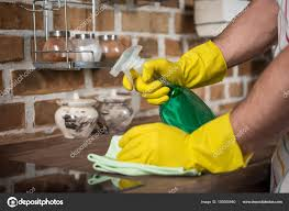 cleaning kitchen cropped image man cleaning kitchen spray bottle rag stock photo