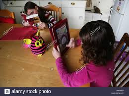 playing a game on the ipad whilst her sister is reading a
