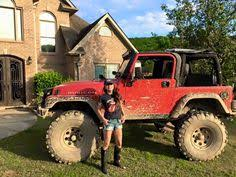 muddy jeep girls that s a happy jeep beside her muddy red lifted big tire