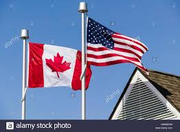 an american flag and a canadian flag flying side by side stock