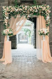 High Vases Wedding Ceremony Flower Arch With A Light Peach Colored Fabric