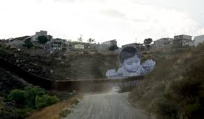 baby on border giant portrait of toddler peers over us mexico