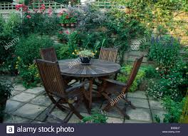 wooden chairs and circular wooden table on paved patio in country