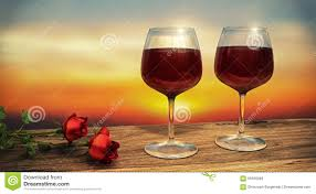 two wine glasses filled with red wine with two red roses during
