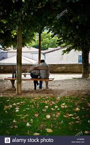 the back of a couple cuddling on a park bench in autumn stock