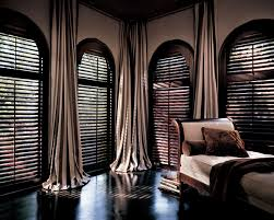 arched louvered shutters from exotic dark wood window treatment