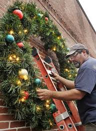putting up christmas lights business j p wallace owner of wallbow s yard care puts up christmas lights