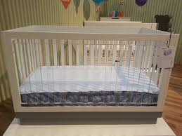 bedroom wooden crib by babyletto with white bedding for nursery