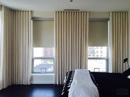 stationary ripple fold panels and blackout roller shades by