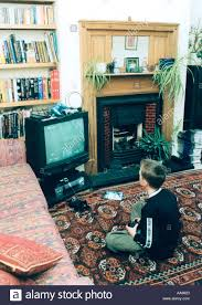 8 year old boy playing playstation football game in living room uk