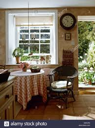 Black Wicker Furniture Circular Clock On Wall Beside Open Door In Cottage Kitchen With