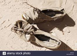 dirty pair old dirty pair of shoes on sand background stock photo royalty
