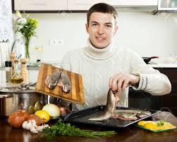 les gar輟ns dans la cuisine sourire cuisson du poisson de gars dans une poêle à la cuisine