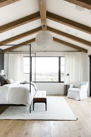promontory project main floor master suite studio mcgee master bedroom in blue grasscloth wallpaper statement chandelier and leather bench