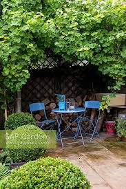 Grape Vine Pergola by Gap Gardens A Secluded Seating Area Under A Pergola Supporting A