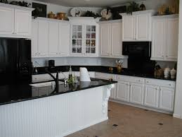 white kitchen cabinets with black countertops two wooden bar stool